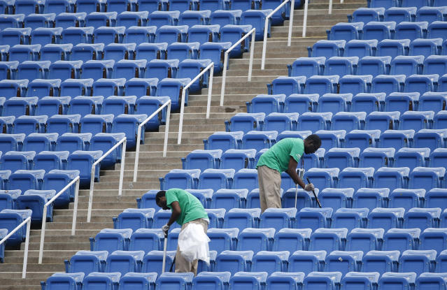 FILE - In this Sept. 10, 2015, file photo, workers clean the empty stands in Arthur Ashe Stadium after the women's semifinal matches were postponed because of rain at the U.S. Open tennis tournament in New York. When he first contemplated the prospect of a U.S. Open without fans because of the coronavirus pandemic, the U.S. Tennis Association's chief revenue officer figured there was no way it could work. Lew Sherr eventually came around to embracing the idea of a closed-door Grand Slam tournament -- if it's held at all; a decision is expected in the next two weeks -- because it still could make money even if millions were forfeited with zero on-site receipts from tickets, hospitality, food and beverage or merchandise sales. (AP Photo/Kathy Willens, File)
