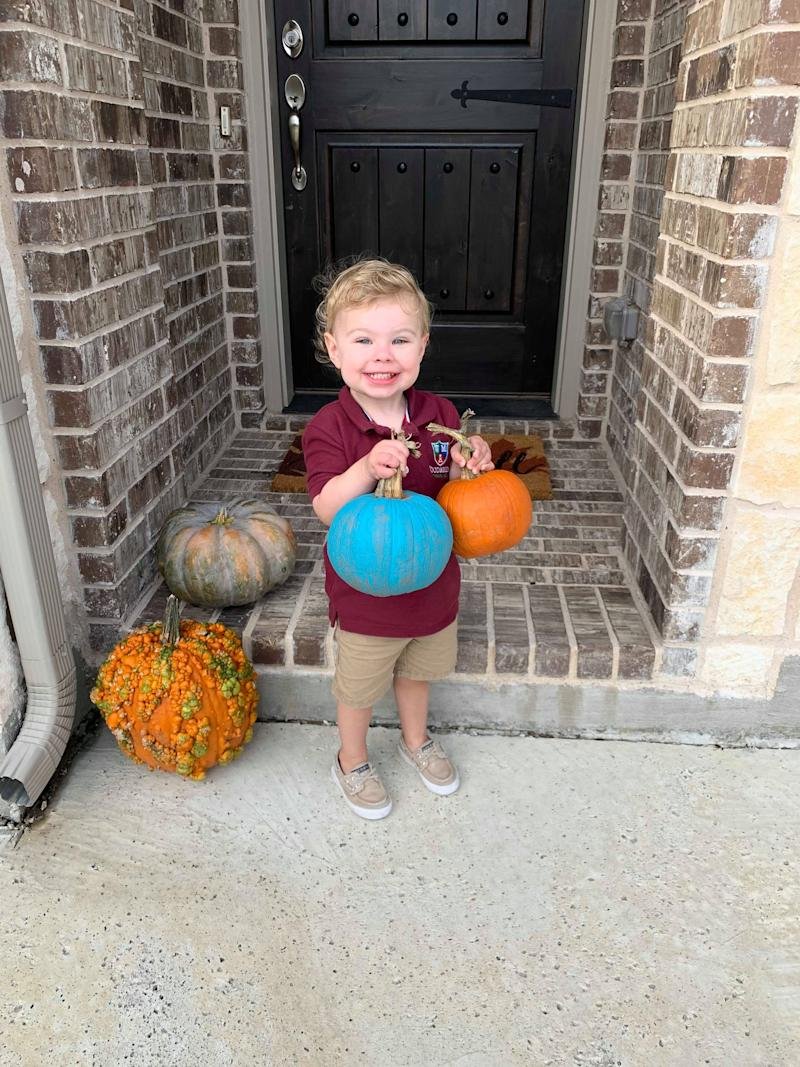 Jackson, 2, poses with a teal pumpkin. He has a tree nut allergy that limits his consumption of candy.