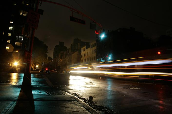 Cars pass through a darkened neighborhood on the west side of Manhattan on Monday, Oct. 29, 2012 in New York. Much of New York was plunged into darkness Monday by a superstorm that overflowed the city's historic waterfront, flooded the financial district and subway tunnels and cut power to hundreds of thousands of people. (AP Photo/Peter Morgan)