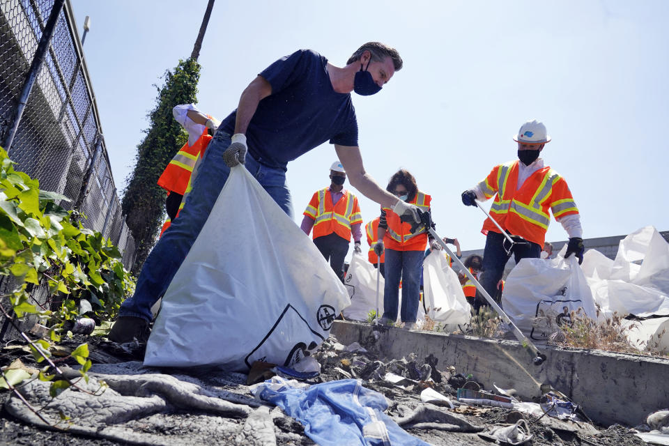 FILE - In this May 11, 2021, file photo, California Gov. Gavin Newsom joins a cleanup effort in Los Angeles. Newsom on Wednesday, July 7, 2021, launched a $1.1 billion plan to clean trash and graffiti from California's highways, roads and other public spaces, in an effort he said will beautify the state and create 11,000 jobs. (AP Photo/Marcio Jose Sanchez, File)
