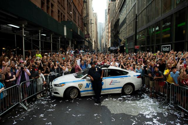 """Fans cheer on members of the World Cup-winning US women's team as they take part in a ticker tape parade for the women's World Cup champions on July 10, 2019 in New York. - Tens of thousands of fans are poised to pack the streets of New York on Wednesday to salute the World Cup-winning US women's team in a ticker-tape parade. Four years after roaring fans lined the route of Lower Manhattan's fabled """"Canyon of Heroes"""" to cheer the US women winning the 2015 World Cup, the Big Apple is poised for another raucous celebration. (Photo by Johannes Eisele/AFP/Getty Images)"""