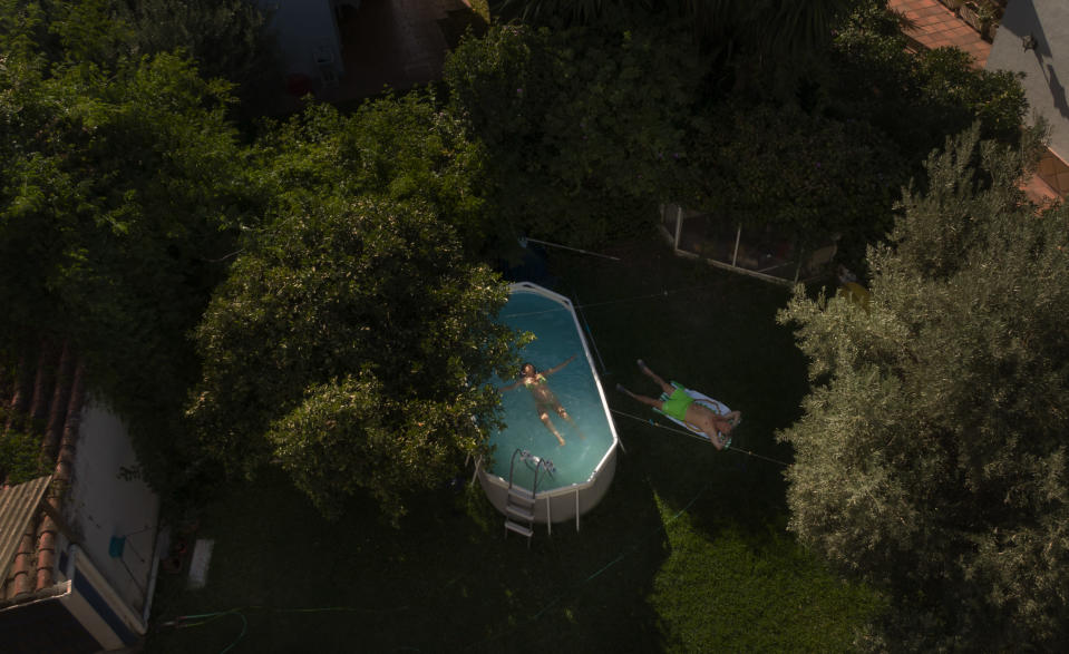 "Manuel Caballos lays on the grass as Esperanza Lafrance swims in a plastic portable pool in the garden of their home in Seville, Spain on Aug. 11, 2020. Caballos had to cancel his vacation due the restrictions of the coronavirus and now says ""the pool is crucial to withstand the heat in the city"". (AP Photo/ Laura Leon)"