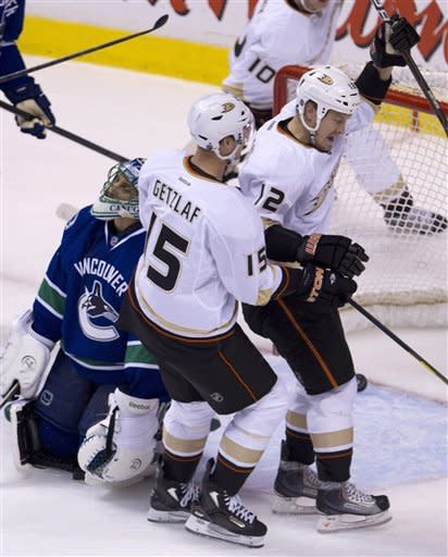 Anaheim Ducks center Ryan Getzlaf (15) celebrates his goal with teammate Anaheim Ducks left wing Niklas Hagman (12) as Vancouver Canucks goalie Roberto Luongo (1) looks on during first period NHL hockey action at Rogers Arena in Vancouver, British Columbia, Tuesday, April, 3, 2012. (AP Photo/The Canadian Press, Jonathan Hayward)