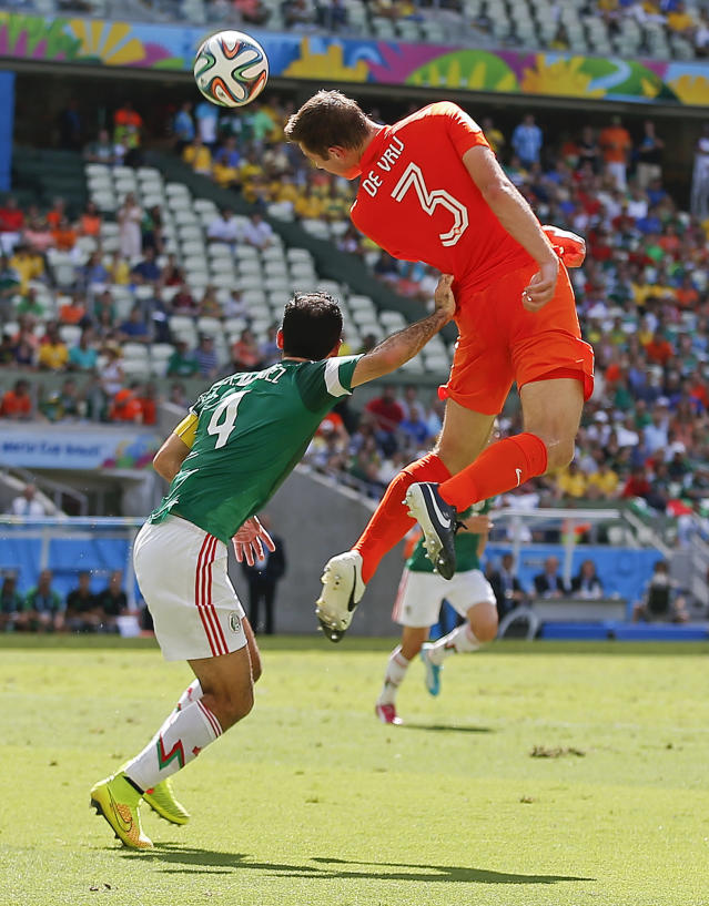 Mexico's Rafael Marquez pushes off Netherlands' Stefan de Vrij as he heads the ball during the World Cup round of 16 soccer match between the Netherlands and Mexico at the Arena Castelao in Fortaleza, Brazil, Sunday, June 29, 2014. (AP Photo/Eduardo Verdugo)