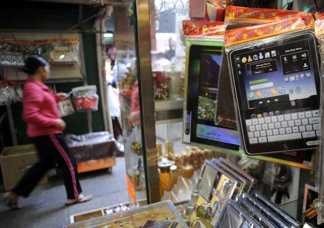 A pedestrian walks past a stall selling paper replicas of computers and smart phones