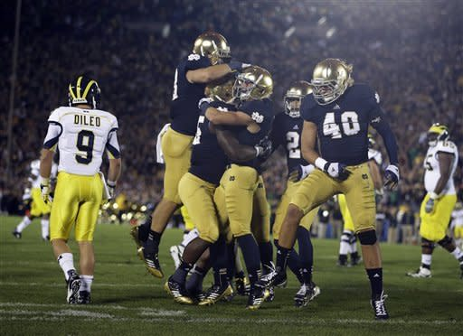 Notre Dame's Nicky Baratti, second from right, is congratulated by teammates after intercepting a pass intended for Michigan's Drew Dileo (9) during the first half of an NCAA college football game Saturday, Sept. 22, 2012, in South Bend, Ind. (AP Photo/Darron Cummings)