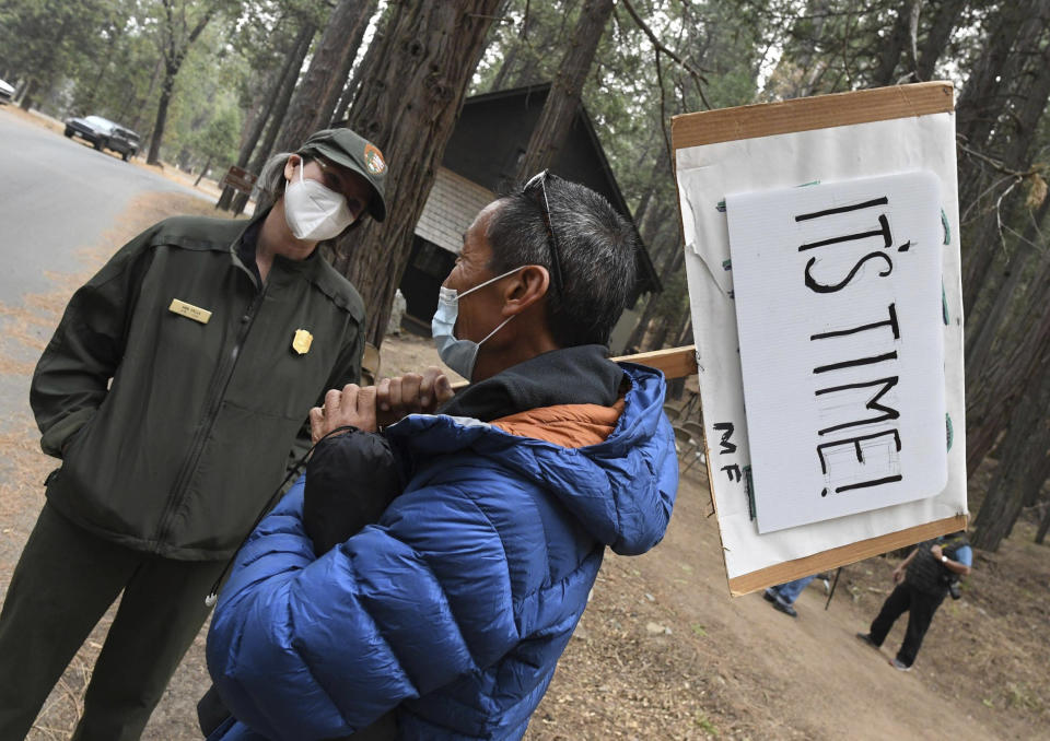 In this Friday, Oct. 1, 2021, photo Eric Leong of San Francisco expresses his feelings in his sign, as he talks with Yosemite Park Ranger Kara Stella in Yosemite National Park, Calif. Officials unveiled on Friday a new sign and exhibit inside a building originally used as a laundry by Chinese workers at Yosemite's Wawona Hotel, formally recognizing Chinese Americans' contributions to the national park's history. (John Walker /The Fresno Bee via AP)