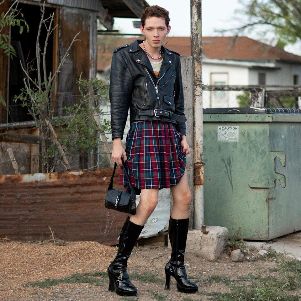 Fish Fiorucci in a Prada skirt, Gucci bag, and Pleaser boots