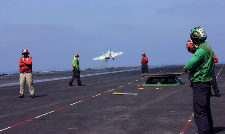 A fighter plane lifts off from the USS George H.W. Bush.