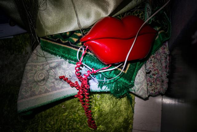 <p>A phone shaped like lips and a prayer rug sit in the corner during a blackout. (Photograph by Monique Jaques) </p>