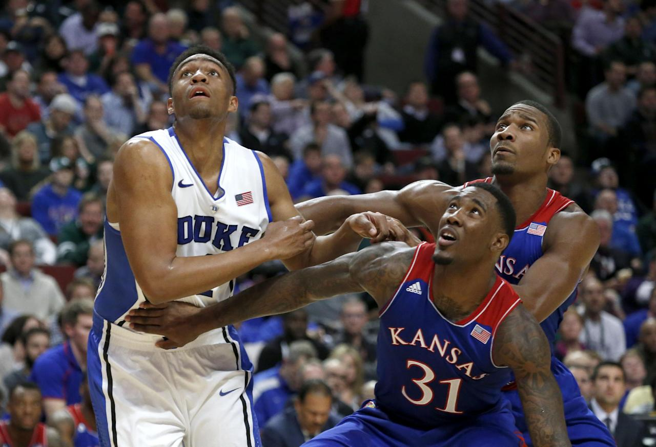 Kansas forward Jamari Traylor (31) and guard Wayne Selden, Jr., right, block out Duke forward Jabari Parker during the first half of an NCAA college basketball game on Tuesday, Nov. 12, 2013, in Chicago. (AP Photo/Charles Rex Arbogast)