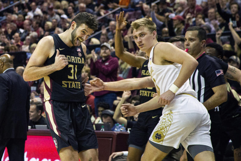 Florida State forward Wyatt Wilkes (31) reacts to his score as he runs backwards in front of Notre Dame guard Dane Goodwin (23) the second half of an NCAA college basketball game in Tallahassee, Fla., Saturday, Jan. 25, 2020. Florida State defeated Notre Dame 85-84. (AP Photo/Mark Wallheiser)