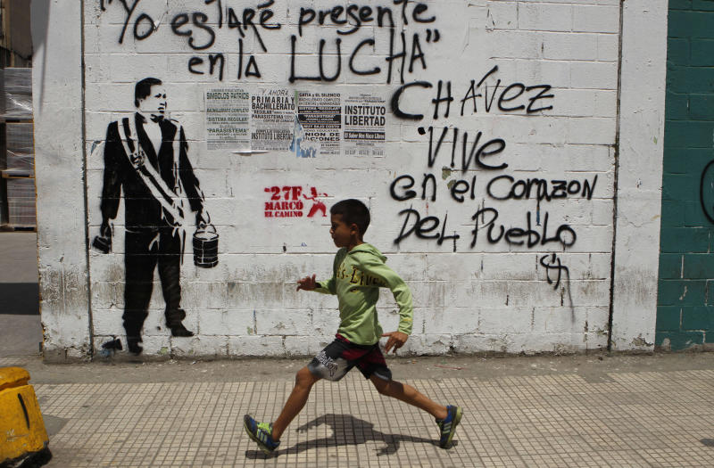 """A child runs past a wall with a stencil graffiti of Venezuela's late President Hugo Chavez and spray-painted writing that reads in Spanish; """"I will be present in the fight. Chavez lives in the heart of the people,"""" in Caracas, Venezuela, Thursday, March 7, 2013. Battling an unspecified cancer, Chavez died Tuesday. His body was taken to the military academy Wednesday, where he started his army career, his flag-draped coffin lying in state as a mile-long line of mourners came to pay homage Thursday. (AP Photo/Esteban Felix)"""