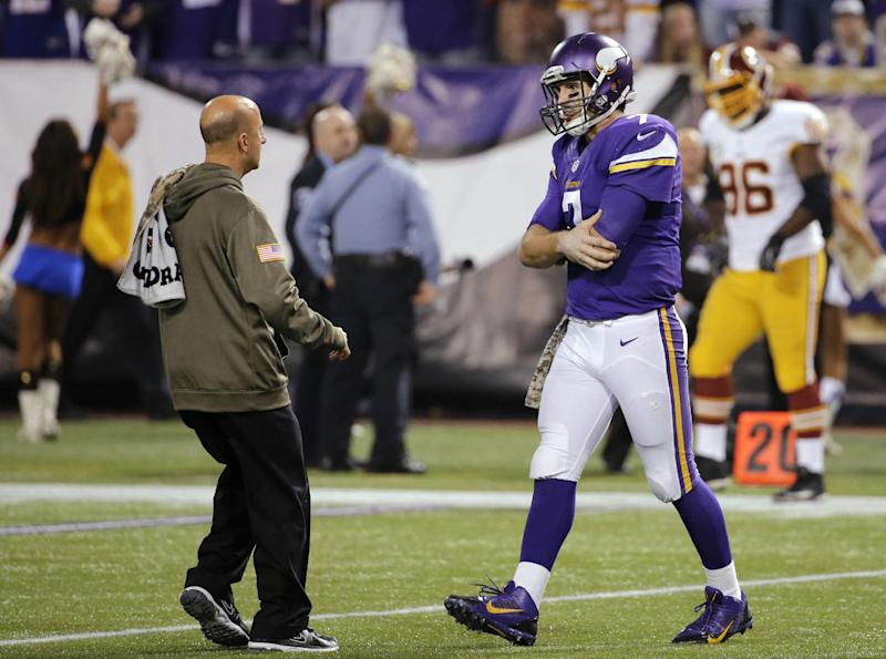 Minnesota Vikings quarterback Christian Ponder, right, is attended to by a trainer after an injury to his left shoulder during the second half of an NFL football game against the Washington Redskins, Thursday, Nov. 7, 2013, in Minneapolis. (AP Photo/Ann Heisenfelt)