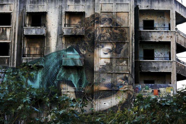In this Nov. 12, 2018, photo, graffiti by Cuban-American artist Jorge Rodriguez-Gerada depicting a boy is painted on a bullet riddled building on the former frontline of the 1975-1990 Lebanese civil war in downtown Beirut, Lebanon. Nearly 30 years after civil war guns fell silent, dozens of bullet-scarred, shell-pocked buildings are still standing _ testimony to a brutal conflict that raged for 15 years and took the lives of 150,000 people.(AP Photo/Hassan Ammar)