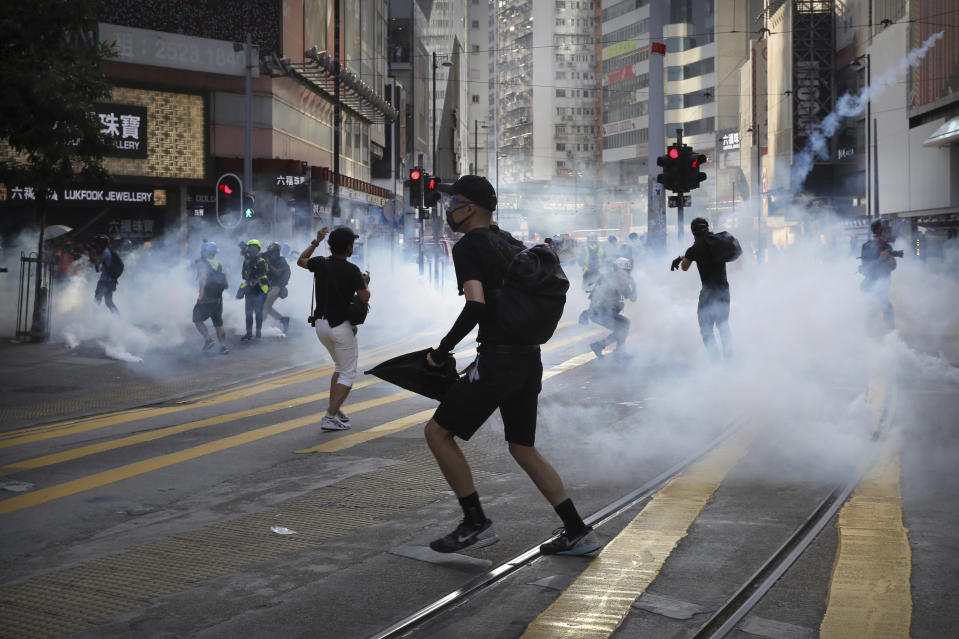 Demonstrators react as police fire tear gas during a protest in Hong Kong, Saturday, Nov. 2, 2019. Hong Kong riot police fired multiple rounds of tear gas and used a water cannon Saturday to break up a rally by thousands of masked protesters demanding meaningful autonomy after Beijing indicated it could tighten its grip on the Chinese territory. (AP Photo/Kin Cheung)