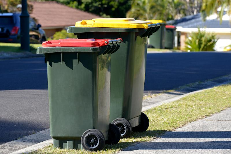 Focus on two Rubbish bins - red lid is rubbish and yellow lid is recycling