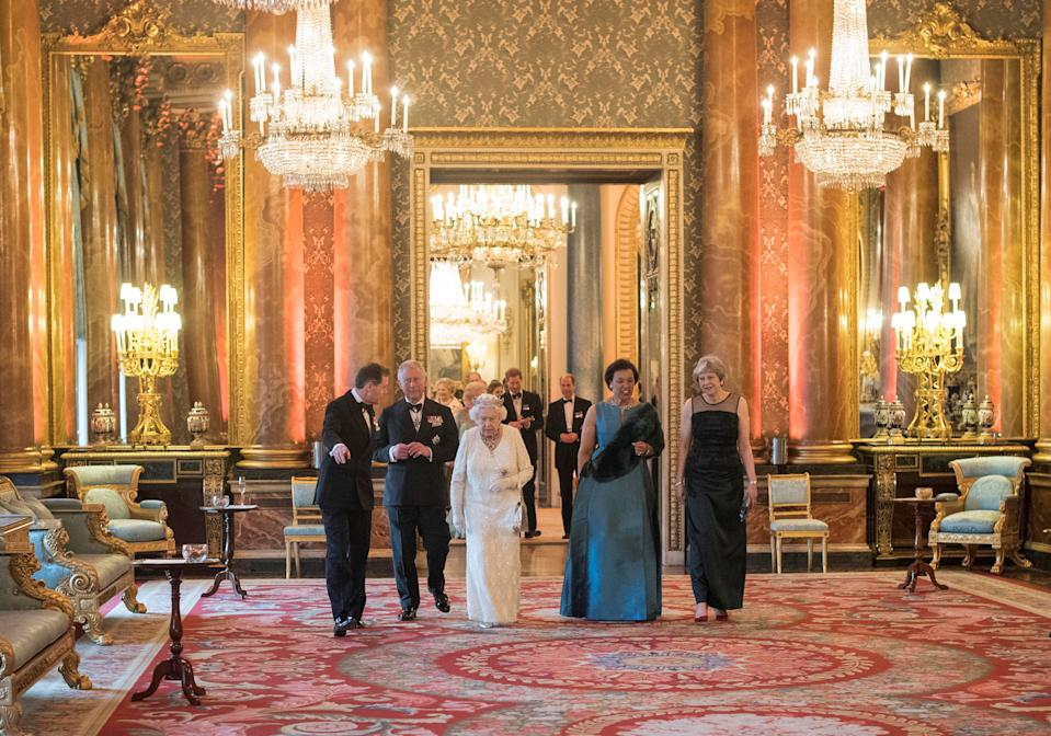 Britain's Queen Elizabeth, Prince Charles, Commonwealth Secretary-General Patricia Scotland and Prime Minister Theresa May walk in the Blue Drawing Room at Buckingham Palace as the Queen hosts a dinner during the Commonwealth Heads of Government Meeting in London, Britain April 19, 2018. Pool/Victoria Jones/via REUTERS