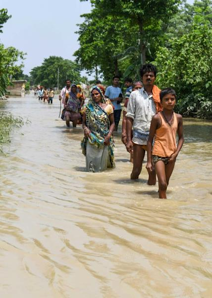 Local residents wade through a flooded road following heavy monsoon rains in Muzaffarpur district in the Indian state of Bihar (AFP Photo/Sachin KUMAR)
