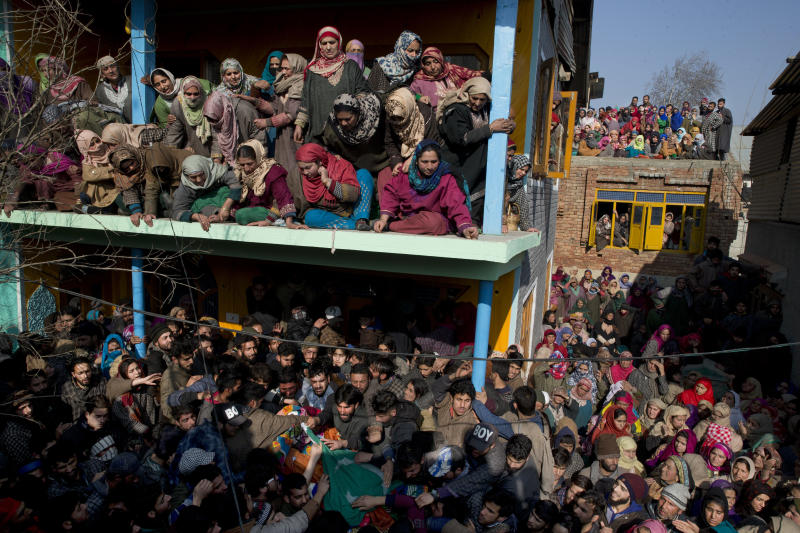 Kashmiri village women watch as men carry the body of a local rebel Muzamil Ahmed Dar during his funeral procession in Rahmoo village south of Srinagar, Indian controlled Kashmir, Saturday, Dec. 29, 2018. Anti-India protests and clashes erupted in disputed Kashmir on Saturday after a gunbattle between militants and government forces killed four rebels, police and residents said. (AP Photo/ Dar Yasin)