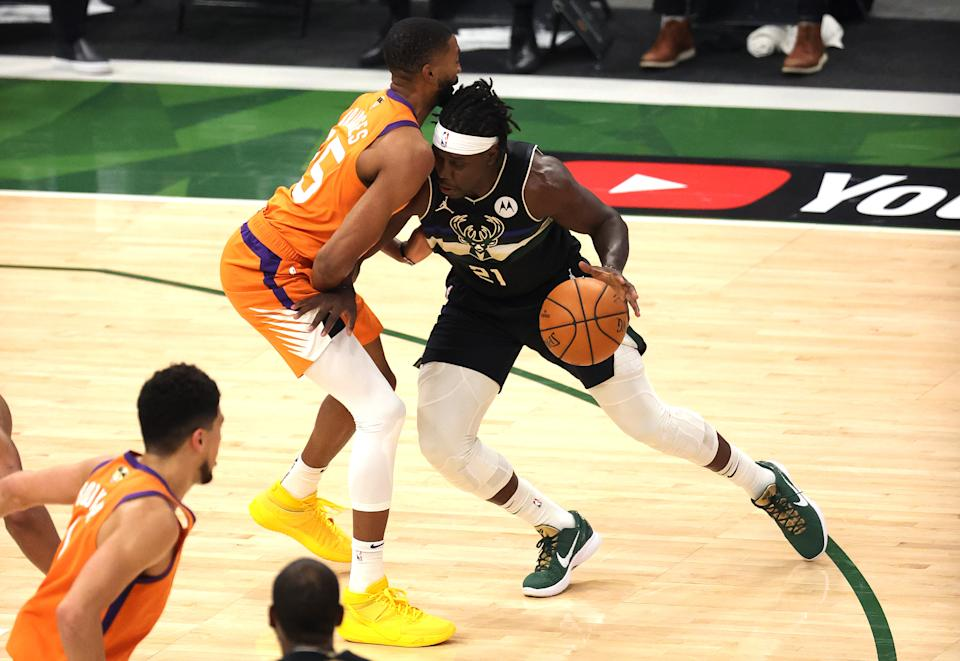 MILWAUKEE, WISCONSIN - JULY 20: Jrue Holiday #21 of the Milwaukee Bucks drives into Mikal Bridges #25 of the Phoenix Suns during the first half in Game Six of the NBA Finals at Fiserv Forum on July 20, 2021 in Milwaukee, Wisconsin. NOTE TO USER: User expressly acknowledges and agrees that, by downloading and or using this photograph, User is consenting to the terms and conditions of the Getty Images License Agreement.  (Photo by Jonathan Daniel/Getty Images)