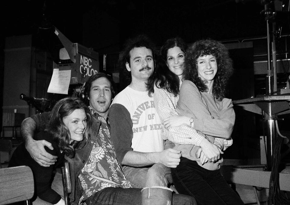 """Comedian Chevy Chase, second from left, joins cast of NBC-TV's """"Saturday Night Live,"""" Feb. 16, 1978 in New York, where he first got his start with the """"Not Ready For Prime Time Players."""" Others are, from left, Jane Curtin, Bill Murray, Gilda Radner, and Laraine Newman. Chase is doing a guest shot on the program. (AP Photo/Marty Lederhandler)"""