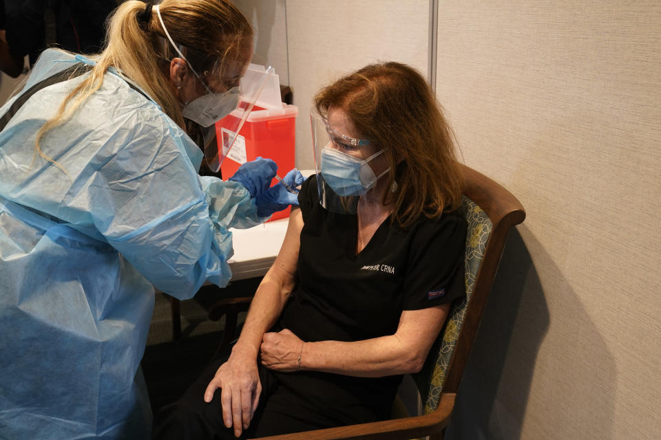 Nurse Eva Diaz administers the Pfizer vaccine to Pam Peters a nurse practitioner at John Knox Village, Wednesday, Dec. 16, 2020, in Pompano Beach, Fla. Nursing home residents and health care workers in Florida began receiving the Pfizer vaccine this week. (AP Photo/Marta Lavandier)