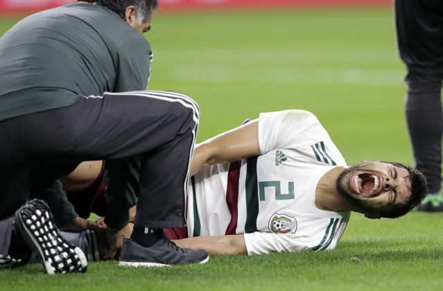 CORRECTS DATE OF PHOTO - A member of the staff checks on Mexico defender Nstor Araujo (2) after Araujo suffered a leg injury in the first half of a friendly soccer match against Croatia in Arlington, Texas, Tuesday, March 27, 2018. (AP Photo/Tony Gutierrez)