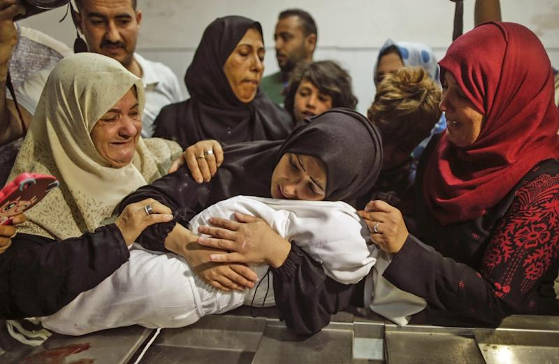 The body of a Palestinian baby who died of tear gas inhalation during protests, according to Gaza's health ministry, is held by her mother at a Gaza City morgue on May 15, 2018 (AFP Photo/MAHMUD HAMS)