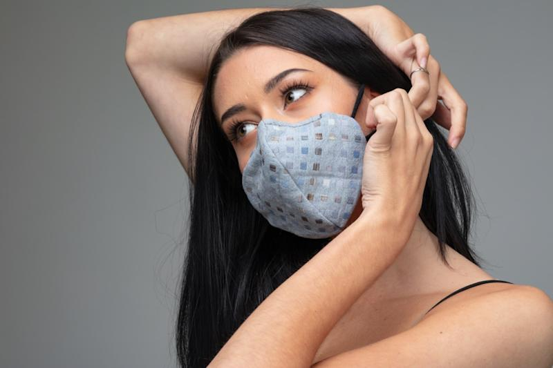 woman adjusting a trendy textile face mask behind her ear.