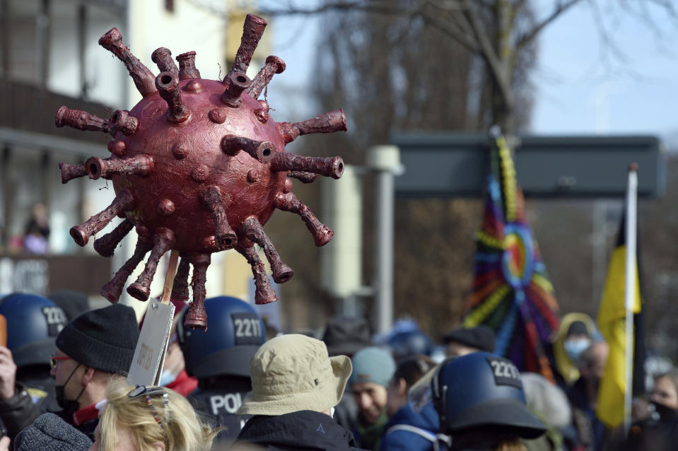 "Participants stand with a Corona virus replica at a rally under the motto ""Free citizens Kassel - basic rights and democracy"" in Kassel, Germany, Saturday, March 20, 2021. According to police, several thousand people were on the move in the city center and disregarded the instructions of the authorities during the unregistered demonstration against Corona measures. (Swen Pfoertner/dpa via AP)"
