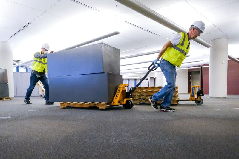 Workers clear furniture from a floor inside the GM Kokomo, Indiana building that General Motors and Ventec Life Systems are converting into use for the production of Ventec ventilators in response to the spread of the coronavirus disease