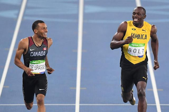 Jamaica's Usain Bolt (R) laughs with Canada's Andre De Grasse after they competed in the Men's 200m Semifinal during the athletics event at the Rio 2016 Olympic Games at the Olympic Stadium in Rio de Janeiro on August 17, 2016 (AFP Photo/PEDRO UGARTE)