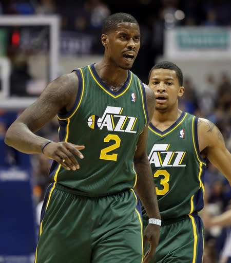 Utah Jazz's Marvin Williams (2) and Trey Burke (3) celebrate a score by Williams as the team goes into a timeout in the first half of an NBA basketball game against the Dallas Mavericks, Friday, Feb. 7, 2014, in Dallas. (AP Photo/Tony Gutierrez)