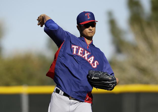 FILE - In this Feb. 17, 2014 file photo, Texas Rangers' Yu Darvish throws as he participates in fielding drills during spring training baseball practice in Surprise, Ariz. Darvish has been scratched from his scheduled start in Monday's, April 31, 2014 season opener because of stiffness in his neck. The announcement Tuesday came a day after Darvish stopped throwing while playing catch. (AP Photo/Tony Gutierrez, File)