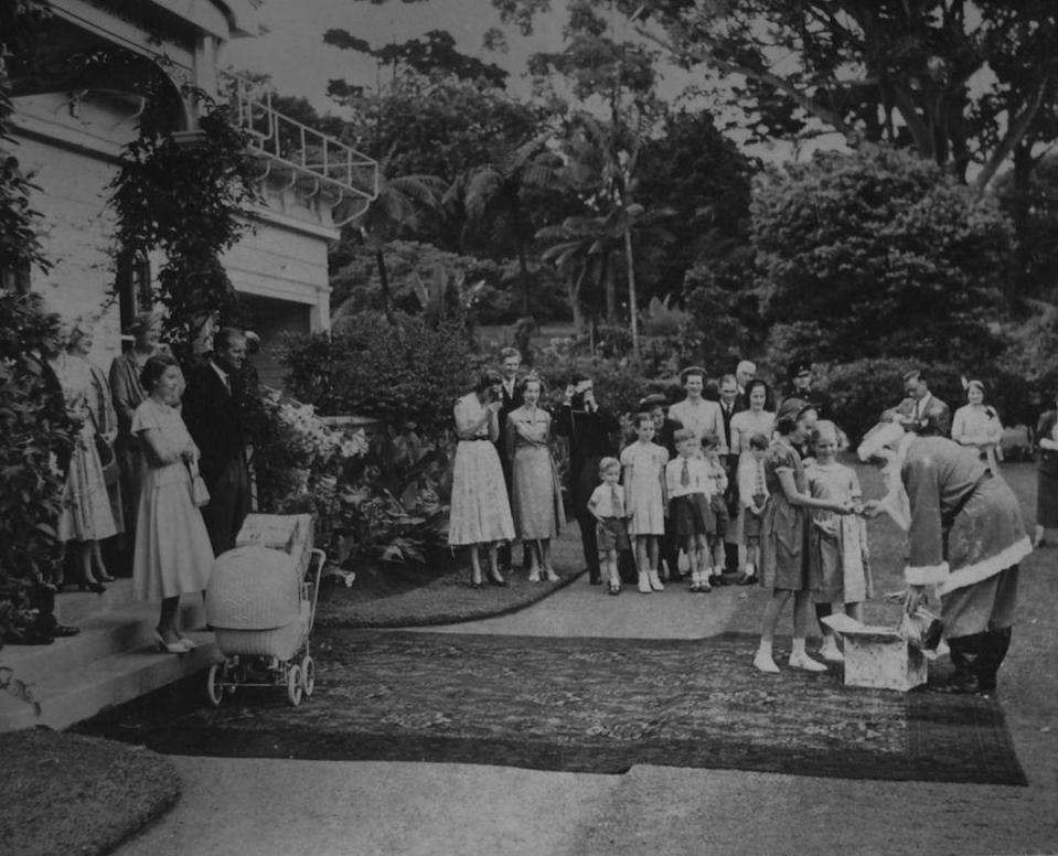 <p>The Queen and the Duke of Edinburgh at Government House in Auckland, New Zealand on Christmas Day. A man dressed as Santa gives presents to the Governor General's daughters.</p>
