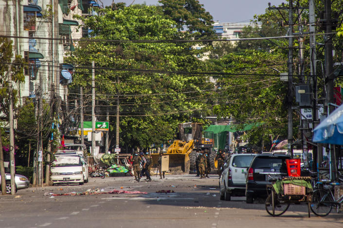 Soldiers and police use a bulldozer to remove improvised barricades installed by anti-coup protesters and residents to secure a neighborhood from security forces in Yangon, Myanmar Thursday, March 18, 2021. (AP Photo)