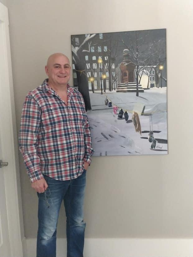 Norman Simard stands next to his painting titled Mittens. Simard started painting when the pandemic was declared, and a year later, two of his pieces made it into an international exhibit.  (Submitted by Norman Simard - image credit)