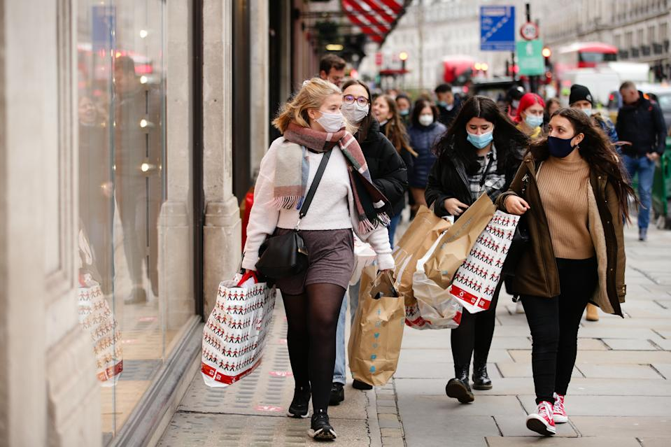 Shoppers wearing face masks carry bags from toy store Hamley's and from fast fashion retailer Primark along Regent Street in London, England, on December 4, 2020. London has returned to so-called Tier 2 or 'high alert' coronavirus restrictions since the end of the four-week, England-wide lockdown on Wednesday, meaning a reopening of non-essential shops and hospitality businesses as the festive season gets underway. Rules under all three of England's tiers have been strengthened from before the November lockdown, however, with pubs and restaurants most severely impacted. In London's West End, Oxford Street and Regent Street were both busy with Christmas shoppers this afternoon, meanwhile, with the retail sector hoping for a strong end to one of its most difficult years. (Photo by David Cliff/NurPhoto via Getty Images)