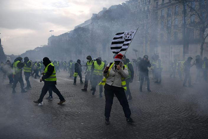 """A man holds a Brittany flag as """"Yellow vests"""" (gilets jaunes) protestors clash with riot police amid tear gas on the Champs Elysees in Paris on Dec. 8, 2018 during a protest of against rising costs of living they blame on high taxes. (Photo: Eric Feferberg/AFP/Getty Images)"""