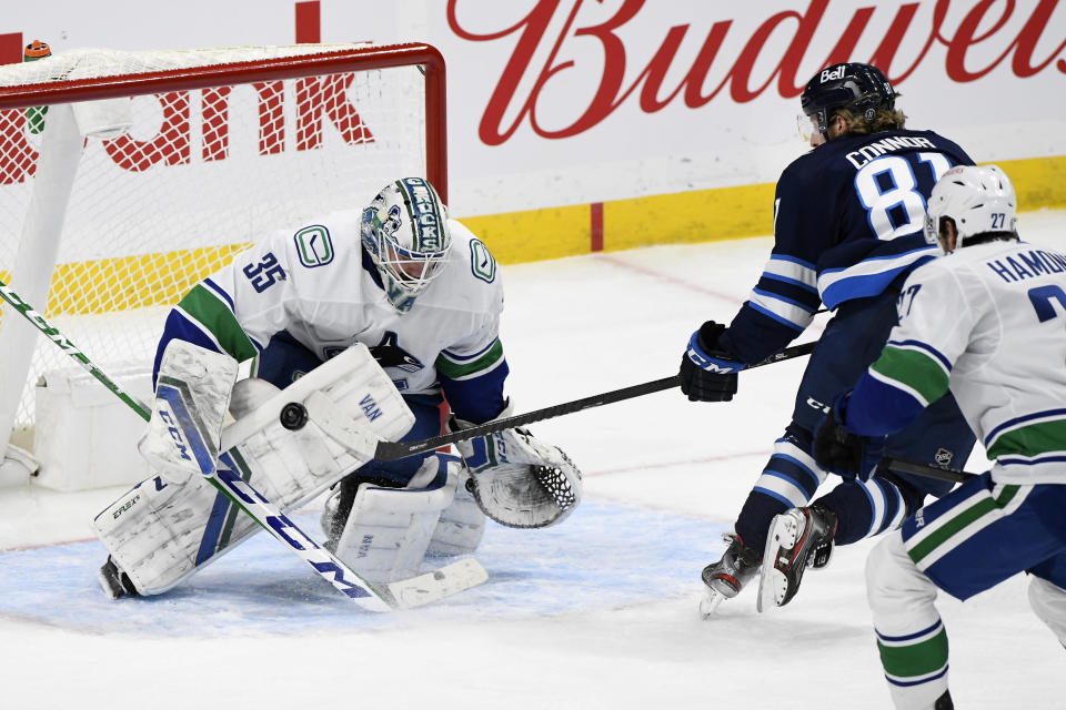 Vancouver Canucks goaltender Thatcher Demko (35) makes a save on Winnipeg Jets' Kyle Connor (81) during the third period of an NHL game in Winnipeg, Manitoba, Monday, May 10, 2021. (Fred Greenslade/The Canadian Press via AP)
