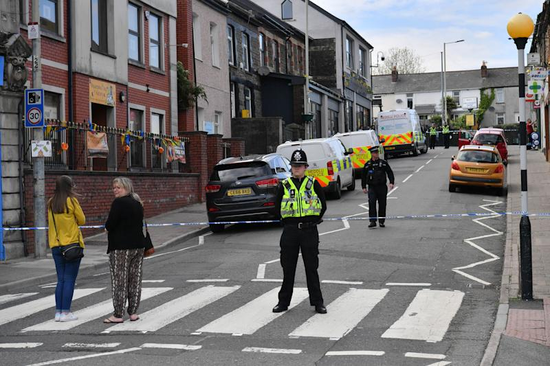 Police at the scene of a reported stabbing in the village of Pen Y Graig in South Wales.