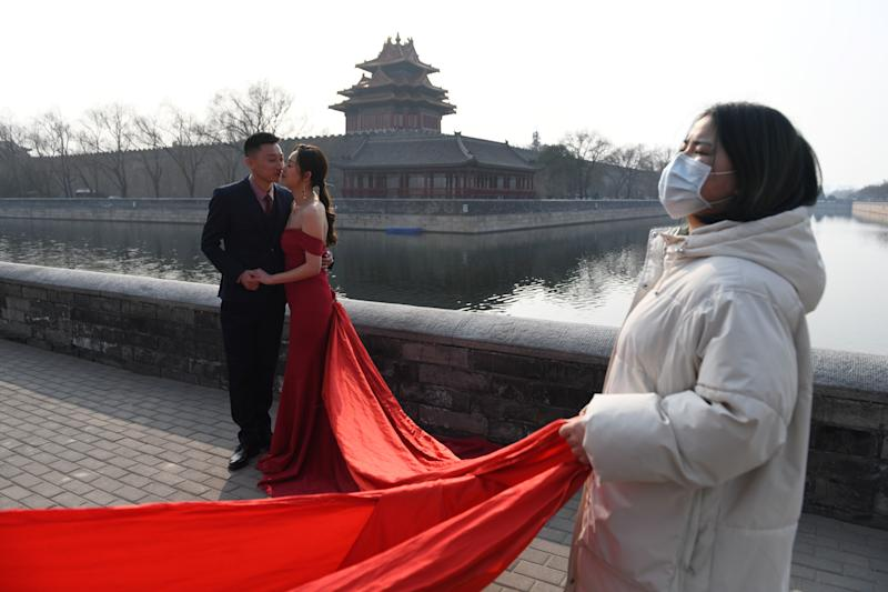 An assistant wears a face mask as a preventive measure against the COVID-19 coronavirus as she helps on a wedding photo shoot next to the Forbidden City in Beijing on February 28, 2020. - China reported 44 more deaths from the novel coronavirus epidemic on February 28 and 327 fresh cases, the lowest daily figure for new infections in more than a month. (Photo by GREG BAKER / AFP) (Photo by GREG BAKER/AFP via Getty Images)