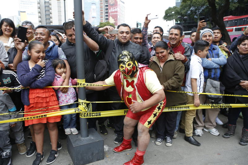 """Mexican wrestler Pinochito poses with the crowd during a """"lucha libre"""" fight in Mexico City, Saturday, Dec. 21, 2019. Mexican wrestling, otherwise known as the """"lucha libre,""""  is a highly traditional form of light entertainment. (AP Photo/Ginnette Riquelme)"""