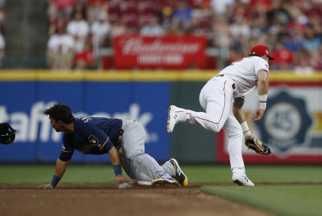 Milwaukee Brewers' Tyler Saladino, left, is safe at second base with a steal as the throw gets away from Cincinnati Reds' Derek Dietrich, right, during the fifth inning of a baseball game, Wednesday, July 3, 2019, in Cincinnati. (AP Photo/Gary Landers)