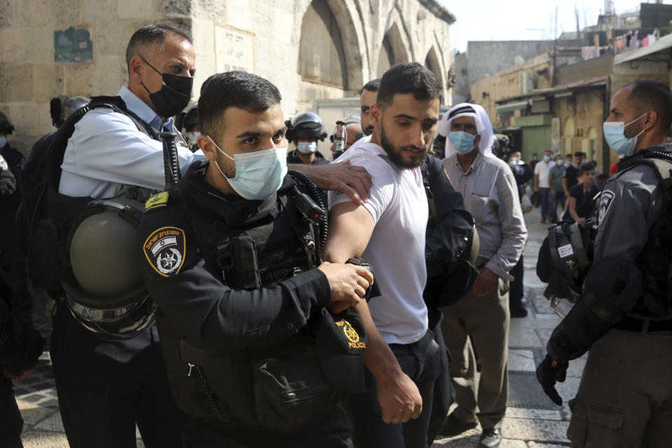 Israeli police detain a man during scuffles in the Old City of Jerusalem after Palestinians protested against French President Emmanuel Macron and the publication of caricatures of the Muslim Prophet Muhammad after Friday prayers at the Dome of the Rock Mosque on Oct. 30, 2020. (AP Photo/Mahmoud Illean)