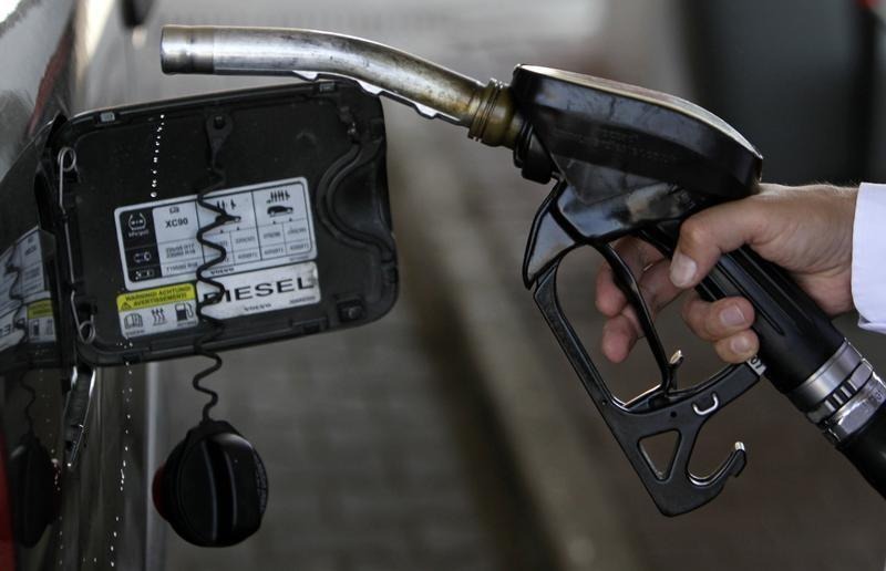 A customer uses the nozzle of a petrol pump at a gas station near Prague