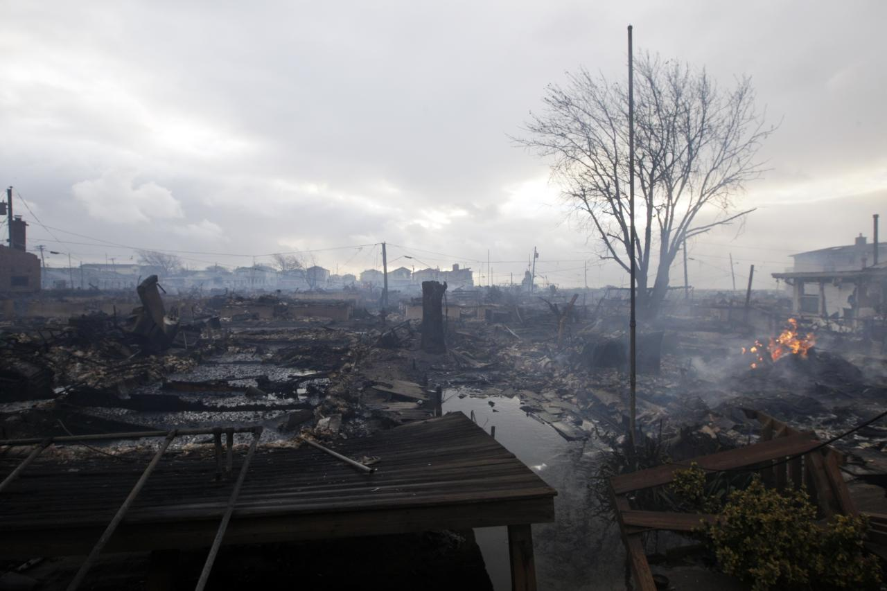 Damage caused by a fire at Breezy Point is shown Tuesday, Oct. 30, 2012, in in the New York City borough of Queen. The fire destroyed between 80 and 100 houses Monday night in the flooded neighborhood. More than 190 firefighters have contained the six-alarm blaze fire in the Breezy Point section, but they are still putting out some pockets of fire. (AP Photo/Frank Franklin II)