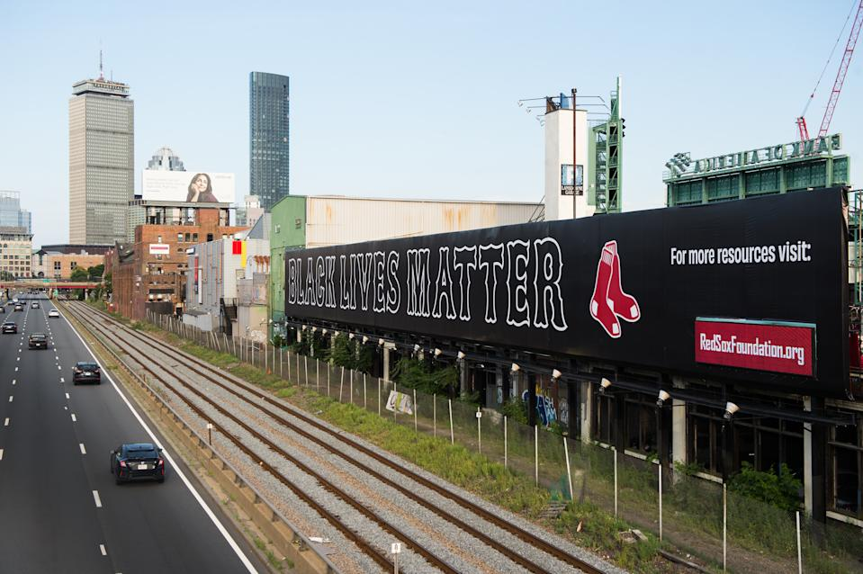 A Black Lives Matter overlooking the Massachusetts Turnpike in the Red Sox's font with the Red Sox logo at the end.
