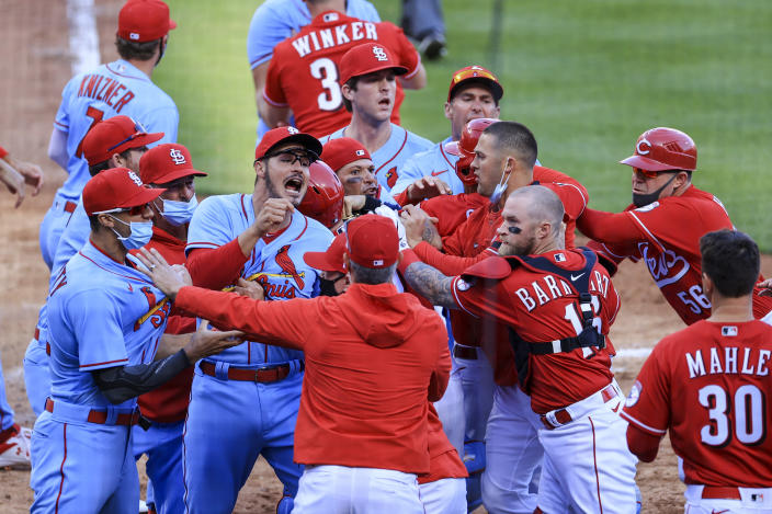 St. Louis Cardinals' Nolan Arenado, center left, reacts alongside teammate catcher Yadier Molina, center, as they scrum with members of the Cincinnati Reds during the fourth inning of a baseball game in Cincinnati, Saturday, April 3, 2021. (AP Photo/Aaron Doster)